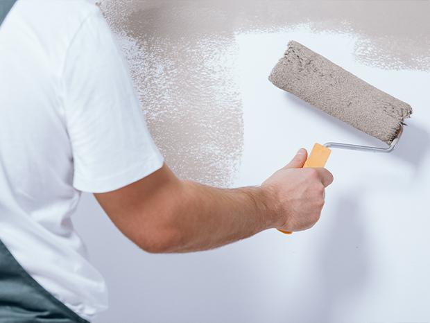 Detailaufnahme wie Mann eine Wand streicht.