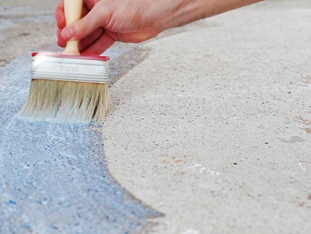 Detailaufnahme wie Beschichtung mit Pinsel auf Beton aufgetragen wird.