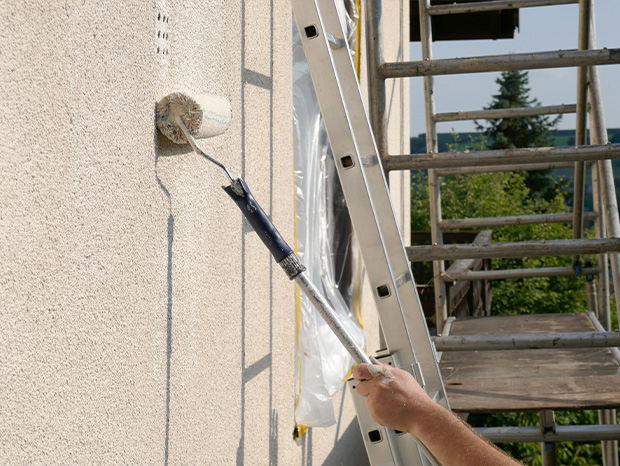 Detailaufnahme wie Fassade gestrichen wird. Leiter und Baugerüst im Hintergrund.