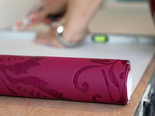 Detailaufnahme wie Tapete zugeschnitten wird.